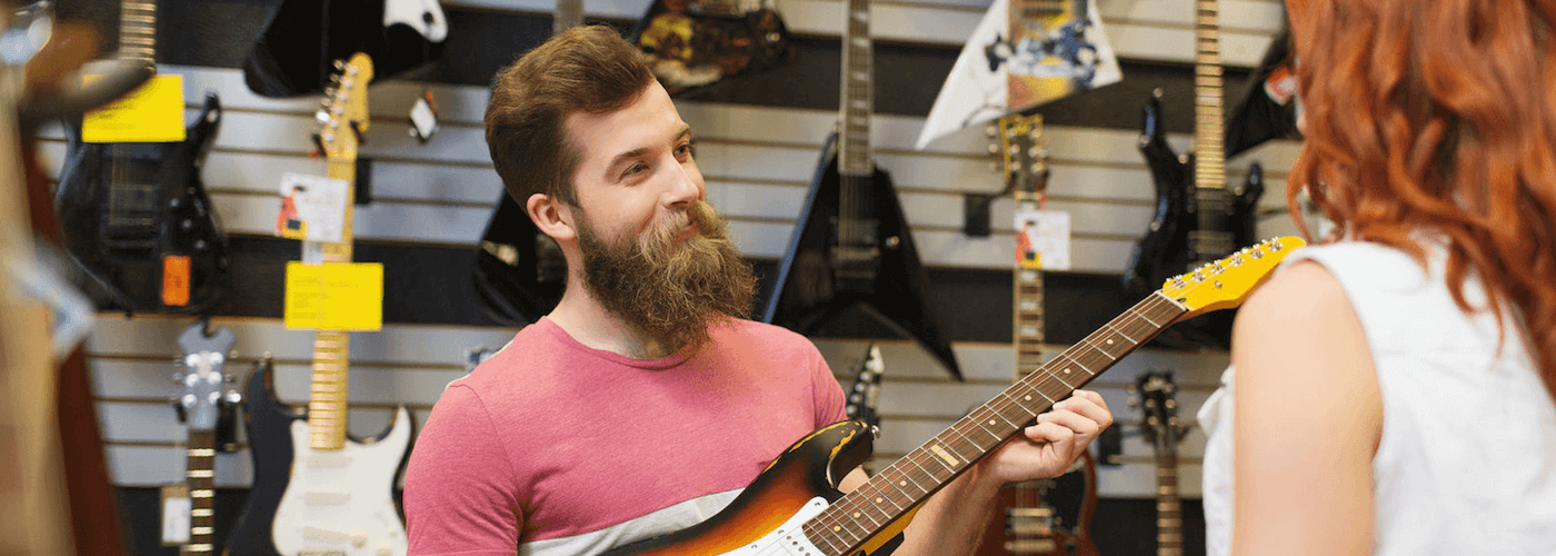 picture of a man selling guitars in a guitar shop